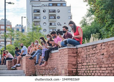 Buenos Aires, Argentina; April 2, 2021: group of young people sitting outdoors at a reading activity, using face masks for the prevention of covid, during the Felba, Publishers and Bookstores Fair