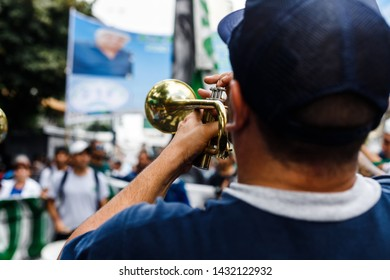 Buenos Aires, Argentina - April 4, 2019: Man seen from behind plays the trumpet in a street workers protest during a strike