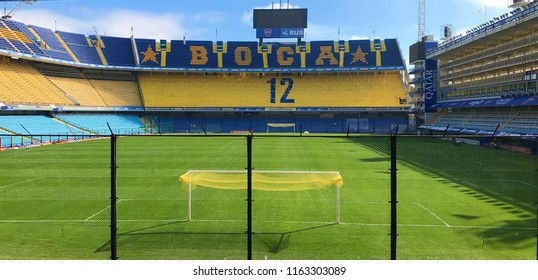 Buenos Aires/ Argentina - August/2018 - Inside view of La Bombonera Stadium - Boca Juniors stadium. Green lawn and bleachers, with writing Boca.