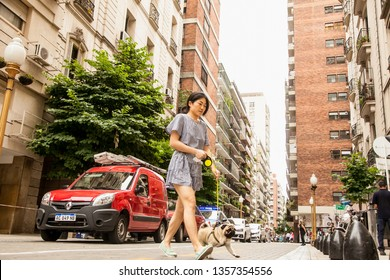 Buenos Aires , Argentina - Dec 27,   2018: Girl walking with her dog on the street of Bueno Aires, Argentina.