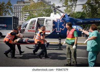 BUENOS AIRES, ARGENTINA - FEB 22: An injured woman is transported in a stretcher next to a helicopter after a train crashed at Once train station in Buenos Aires on February 22, 2012.
