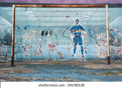BUENOS AIRES, ARGENTINA, FEBRUARY 15: Damaged graffiti in popular area of Boca shows football player ready to shoot at the ball on February 15, 2011 Buenos Aires.