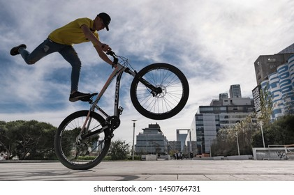 Buenos Aires, Argentina - May 25 2019: BMX biker doing an advanced trick with the city on background.