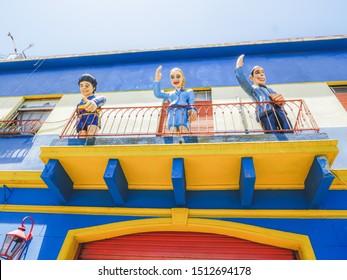 Buenos Aires, Argentina - Novembre 2017: Diego Maradona, Evita Peron, Carlos Gardel in a balcony greeting the tourist at Caminito, La Boca. Colourful puppets and houses.