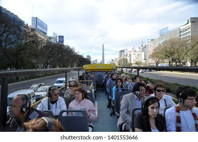BUENOS AIRES / ARGENTINA - OCTOBER 3 2009: A group of tour bus passengers ride on the open-air upper deck of the big yellow Buenos Aires Bus driving along Avenida 9 de Julio away from Obelisco.