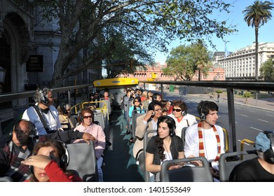 BUENOS AIRES / ARGENTINA - OCTOBER 3 2009: A group of tour bus passengers ride on the open-air upper deck of the big yellow Buenos Aires Bus.
