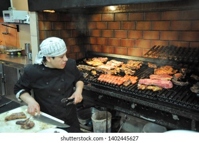 "BUENOS AIRES / ARGENTINA - OCTOBER 6 2009: Grill chef at tenedor Libre restaurant ""Parilla Libre"" with various kinds of meat cooking on the grill."
