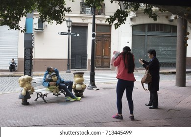 BUENOS AIRES, ARGENTINA - SEPTEMBER 2017 - unidentified tourist people taking photos of Mafalda, a child characters book, on the bech in San Telmo