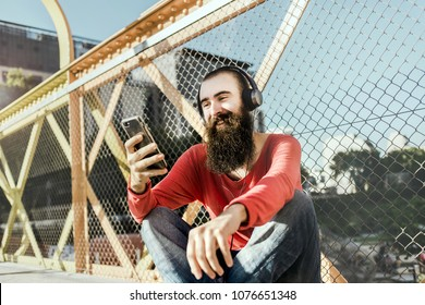 Buenos Aires, Argentine - January 2018: bearded man with Smartphone and Headphones on Science Park Bridge