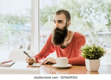 Buenos Aires, Argentine - January 2018: bearded man writing notes in Science Park Coffeshop