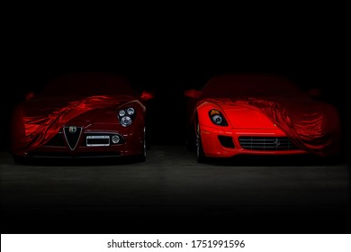 Buenos Aires, Year 2016: Front view of two Italian supercars covered with a cloth cover. Alfa Romeo 8C Competizione and Ferrari 599 GTB Fiorano. Expensive exotic cars, dark background.