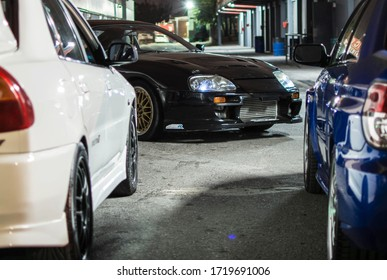 Buenos Aires, Year 2016: Japanese sports cars. A Toyota Supra in the middle of two cars, Subaru Impreza STI and Mitsubishi Lancer Evolution 6. JDM cars in the night.