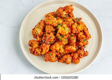 Buffalo Cauliflower Wings on a Baking Sheet.  Popular Baked Cauliflower Appetizer Photo.. Barbecue Cauliflower Wings - Vegan Food