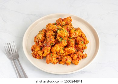 Buffalo Cauliflower Wings on a White Plate with Forks on White Background.