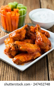 Buffalo chicken wings with cayenne pepper  sauce served hot with celery sticks and carrot sticks with blue cheese dressing for dipping
