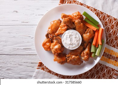 buffalo chicken wings with cheese sauce and celery on the table. horizontal view from above