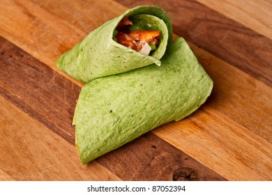 Buffalo chicken wrap in spinach tortilla on wooden surface
