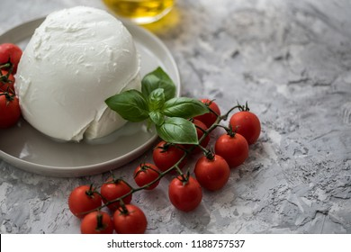 Buffalo mozzarella cheese ball with cocktail tomatoes, basil and olive oil on plate
