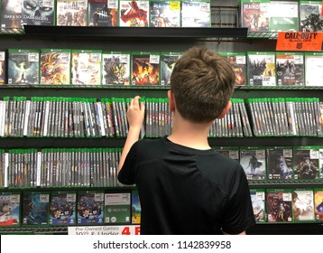 Buffalo, NY - JUNE 1, 2018: A young boy is buying an xbox one video game at a store for a gamer technology concept.