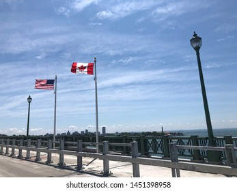 Buffalo, NY/USA- July 14,2019: American flag and Canadian flag blowing side by side on the US and Canada Peace Bridge Border
