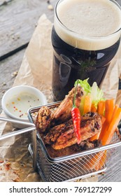 Buffalo style chicken wings in basket with glass of beer