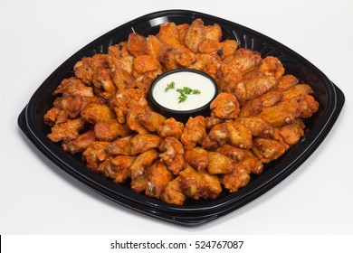 Buffalo wing platter for office or sports party surrounding a dish filled with ranch dressing and garnished with parsley. White background.