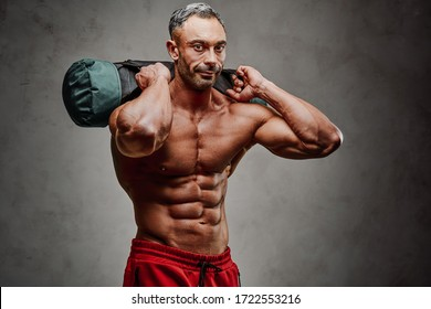 Buffed strong man practicing functional training powerlifting workout exercises with a weight bag and smiling, close-up photo
