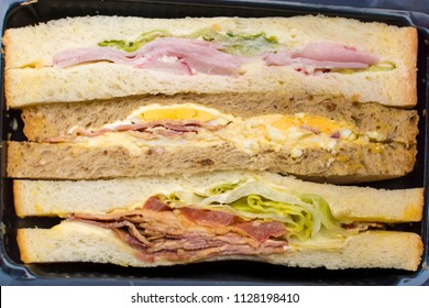 Buffet sliced sandwiches cut with different filling - ham, salad, radish, egs, bacon, dried meat, whole grain bread