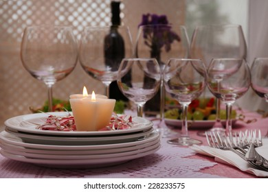 Buffet table with dishware and candles waiting for guests