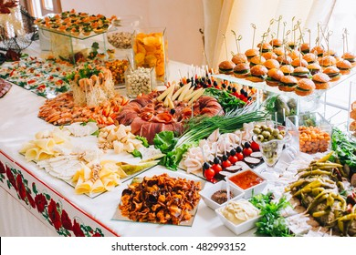 Buffet table of reception with burgers, cold snacks, meat and salads