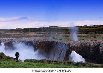 Bufones de Pria in the coast near a cliff in Asturias, Spain. A photographer takes pictures of the scene.