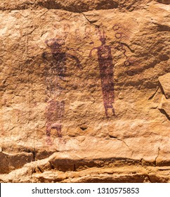 A bug eyed extra terrestrial looking anthropomorph and another with antennae holding a snake near the Head of Sinbad pictograph panel in the San Rafael Swell, Utah, United States.
