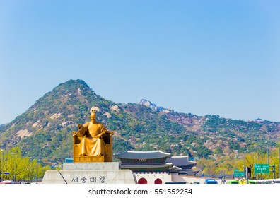 Bugaksan mountain in background behind Gyeongbokgung Palace entrance and sitting statue of King Sae Jong Dae Wang written in Korean language on base, on blue sky day in center Seoul, South Korea. Left