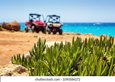 Buggy parked convertible car on the beach near the sea and clear blue sky with green plants. Off-road car is major tourists attraction and popular touristic transport for rent at Cyprus, Nissi beach.