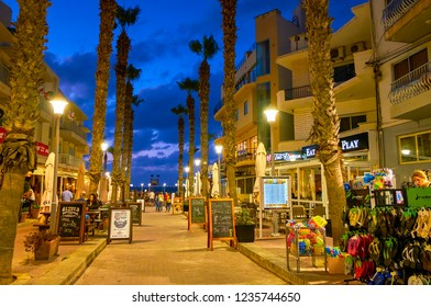 BUGIBBA, MALTA - JUNE 14, 2018: Evening Bay Square with a view on souvenir stalls, popular cafes, restaurants and palm alley along the shopping zone, on June 14 in Bugibba.
