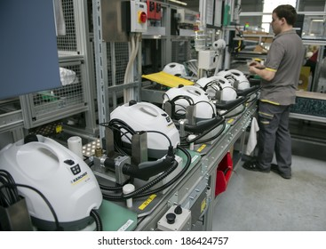 """BUHLERTAL, GERMANY - MARCH 30, 2014:  Machine-building plant of the company Karcher """"Alfred Karcher GmbH & Co. KG"""".  Unidentified worker collects high-pressure apparatus."""