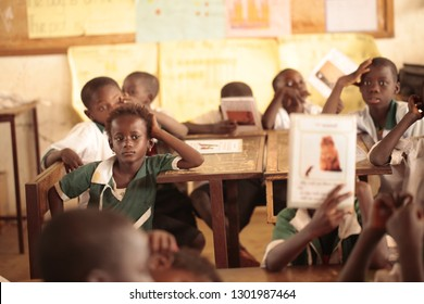 Buiba Mandinka, the Gambia, Africa, October 25, 2015: inside of small village classroom with african kids in school uniforms, sitting by vintage metal and wooden desks, looking into camera