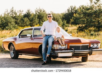 Buick Riviera in retro style. Unique car. Dad and son are sitting on the hood of a retro car on sunset.