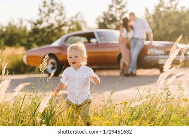 Buick Riviera in retro style. Unique car on sunset. Parents are standing near the car and kissing in the background, the son plays running away from them in the foreground.
