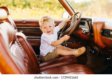 Buick Riviera in retro style. Unique car. Cute blond boy is sitting behind the wheel of a retro car