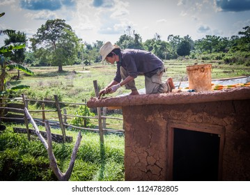 Buider making roof of mud house.