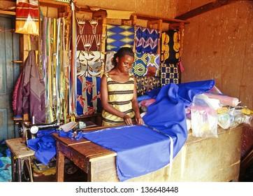 BUIKWE REGION, AJIJJA, UGANDA - JULY 26: An unidentified village dressmaker in her shop on July 26, 2004 in village Ajijja, Uganda. Typical colored dresses are the pride of the local women.