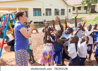 Buikwe, Uganda. June 28 2017. A foreign missionary (Caucasian, called 'mzungu' or 'muzungu' by the locals) blowing soap bubbles and Ugandan children are having fun at that.