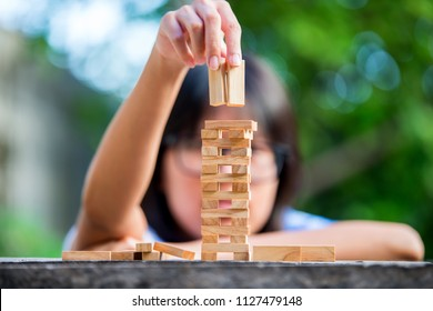 The to build game  tower stack from wooden blocks toy and hand take on block. Education concept.Photo by select focus.
