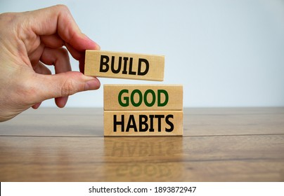 Build good habits symbol. Wooden blocks with words 'build good habits'. Male hand. Beautiful wooden table, white background, copy space. Business, psychological and build good habits concept.