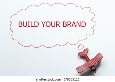 BUILD YOUR BRAND red toy airplane with talk bubble on white background
