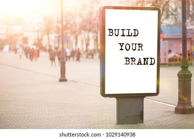 BUILD YOUR BRAND text on a billboard in the center of the city. Business idea.