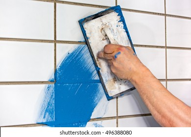Builder applying colorful blue grouting to newly laid white tiles on a wall using a rubber trowel to apply the mortar