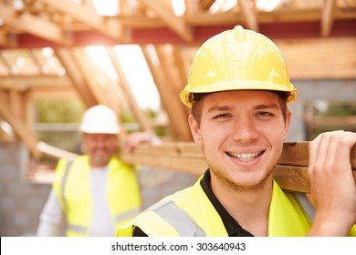 Builder And Apprentice Carrying Wood On Construction Site