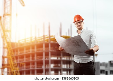 The builder, the architect holds in his hand architectural drawings on the background of the construction site. Concept architecture, construction, engineering, design, repair. Copy space